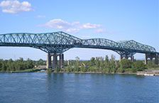 The Champlain Bridge is a steel truss cantilever bridge with approach viaducts constructed of prestressed concrete beams supporting a prestressed concrete deck paved with asphalt. Wikipedia
